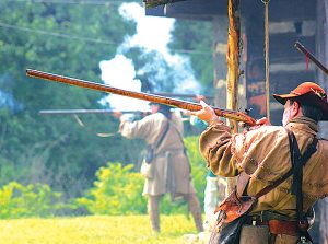 Photo by Abigail Whitehouse While Native Americans attack from the treeline, men aim their guns and fire as they defend Logan's Fort during the reenactment of the Siege of 1777.
