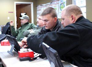 Photo by Abigail Whitehouse As Sgt. Sim Thacker and Deputy Rob Oney listen to discussion, Deputies Chase Marcum, right, and Michael Mullins try out the new devices.
